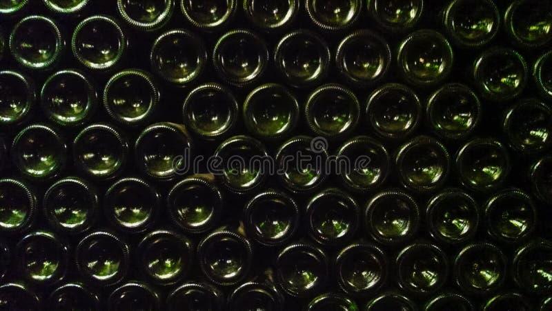 Bottiglie di birra verde scuro impilate fino alla forma una parete fotografia stock