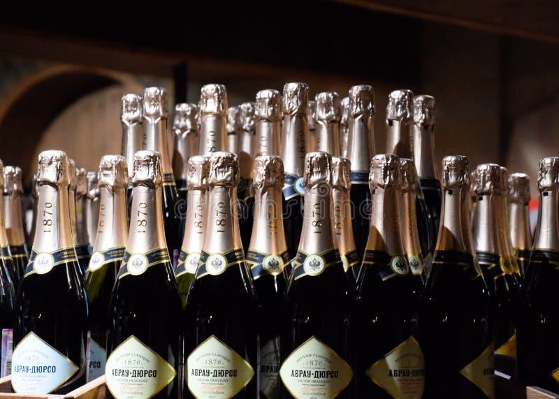 Bottiglie di champagne sul contatore Scaffali con vino e champagne nella cantina del deposito Contatore alla cantina fotografia stock