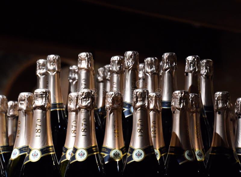 Bottiglie di champagne sul contatore Scaffali con vino e champagne nella cantina del deposito Contatore alla cantina fotografie stock libere da diritti
