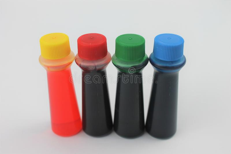 Bottiglie di colorante alimentare su un fondo bianco isolato fotografie stock