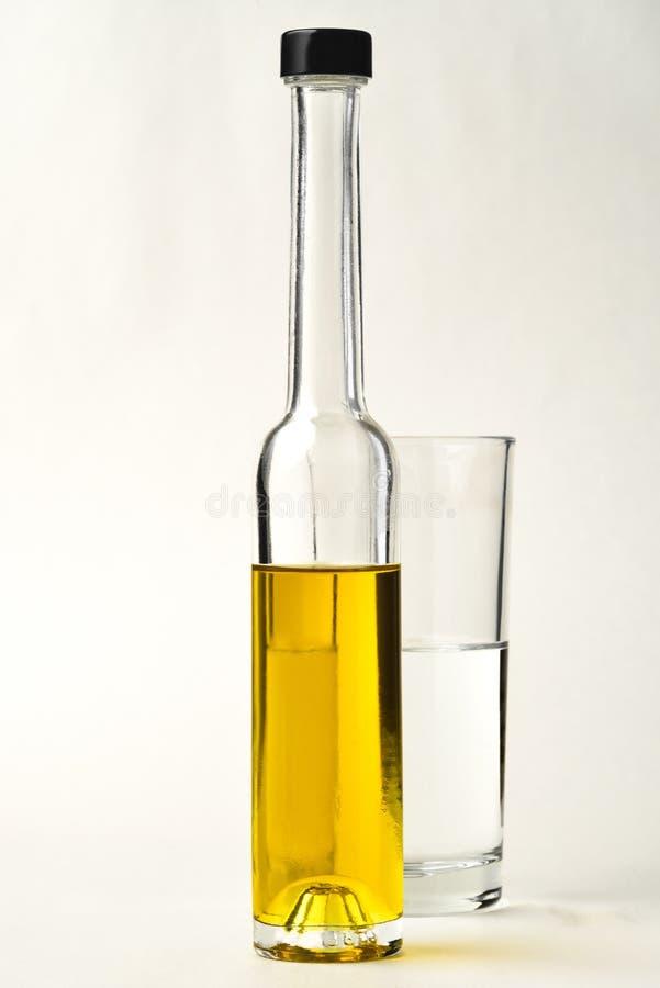 Bottiglie di Olive Oil con bicchiere d'acqua fotografia stock