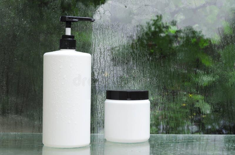 Bottiglie di plastica bianche dei prodotti cosmetici per la presa della doccia Gocce di acqua sullo scaffale di vetro fotografia stock