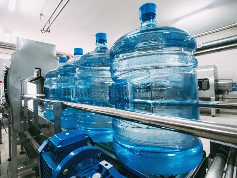 Bottiglie di plastica blu con acqua potabile purificata sulla linea di produzione del trasportatore automatico Fabbrica di acqua immagine stock