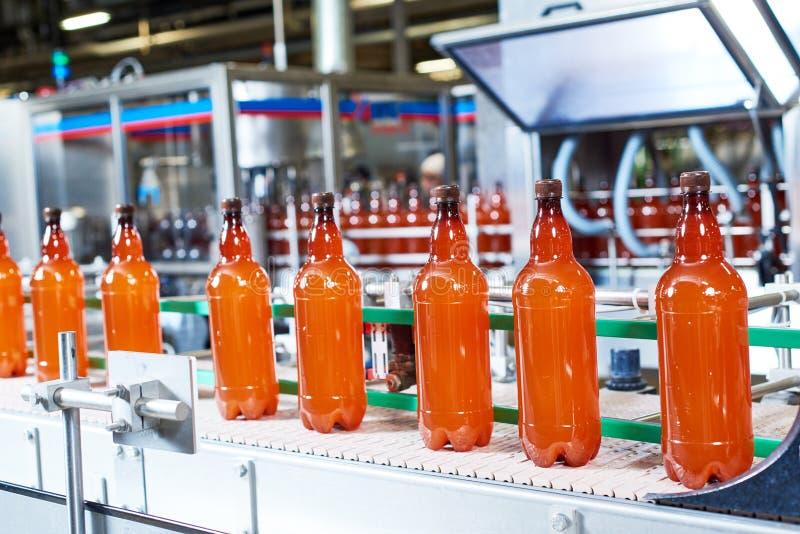 Bottiglie di plastica con birra o la bevanda gassosa che passa trasportatore fotografia stock libera da diritti