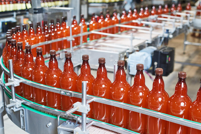 Bottiglie di plastica con birra o la bevanda gassosa che passa trasportatore fotografia stock