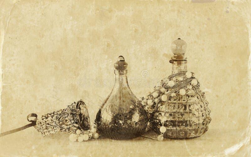 Bottiglie di profumo antiche d'annata, sulla tavola di legno retro immagine filtrata Foto di vecchio stile immagine stock