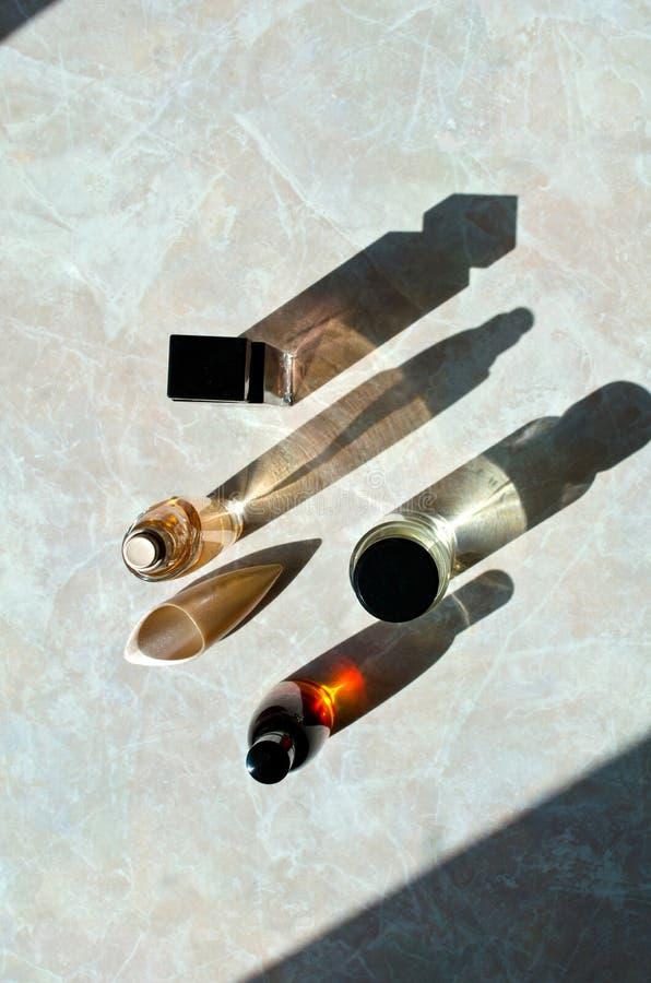 Bottiglie di profumo con le ombre lunghe immagini stock