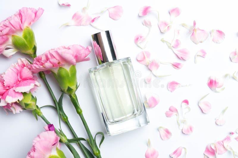 Bottiglie di profumo e garofani rosa su fondo bianco fotografia stock libera da diritti