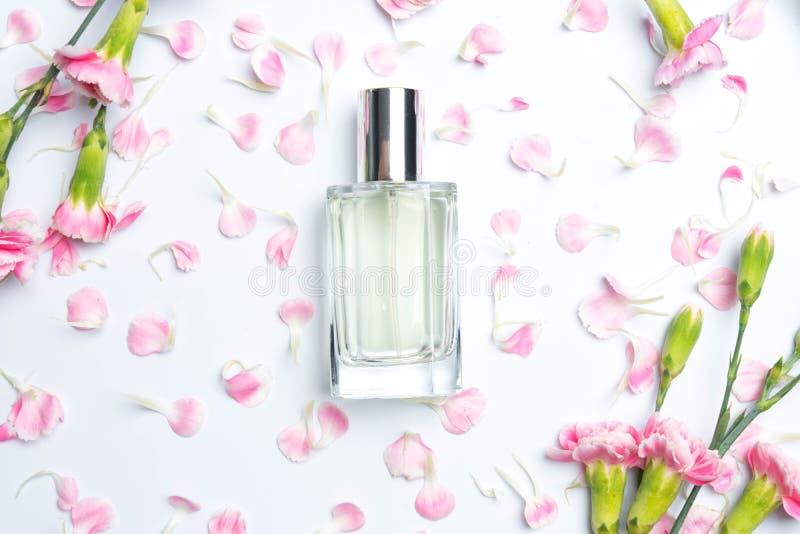 Bottiglie di profumo e garofani rosa su fondo bianco fotografie stock