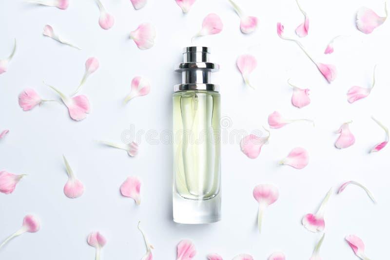 Bottiglie di profumo e garofani rosa su fondo bianco immagini stock libere da diritti