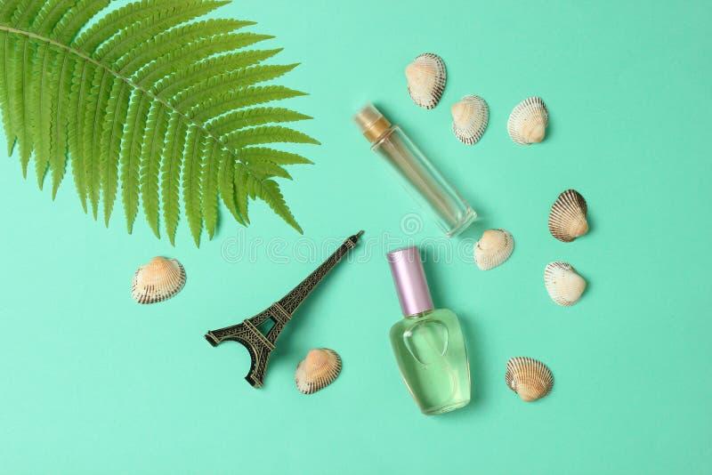 Bottiglie di profumo, una statuetta della torre Eiffel, foglia della felce su fondo pastello blu summertime minimalism stile pian fotografia stock libera da diritti