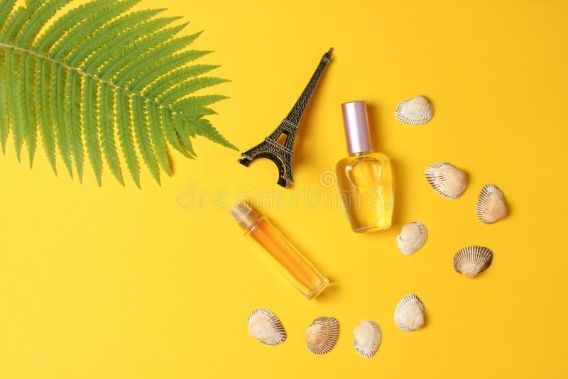 Bottiglie di profumo, una statuetta della torre Eiffel, foglia della felce su un fondo pastello giallo summertime minimalism stil immagini stock libere da diritti