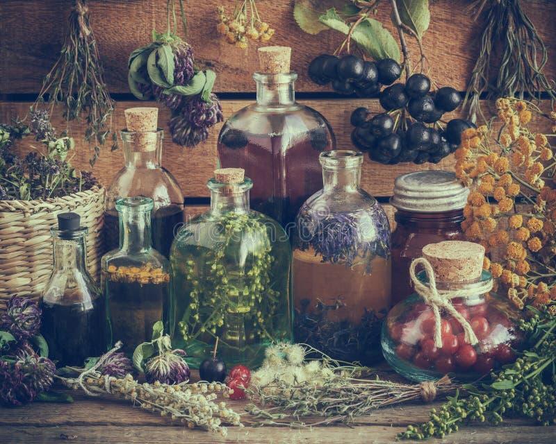 Bottiglie di tintura, di pozione, di olio, delle bacche sane e delle erbe immagine stock