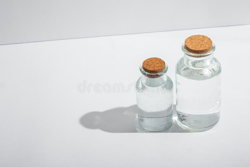 Bottiglie di vetro con i coperchi del sughero su un fondo bianco immagini stock