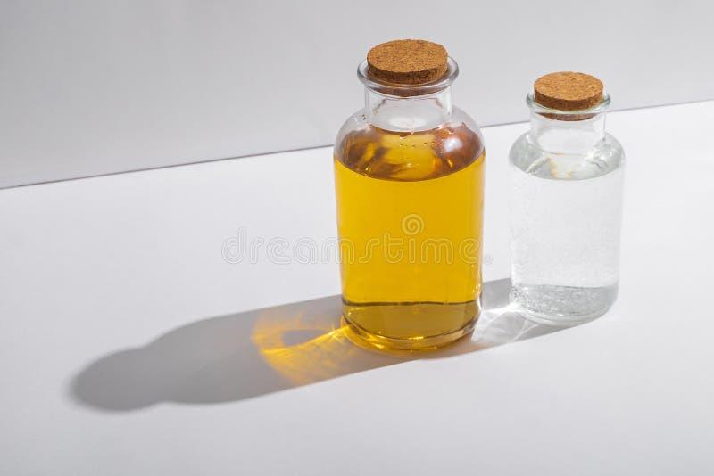 Bottiglie di vetro con i coperchi del sughero su un fondo bianco, vista laterale immagine stock libera da diritti