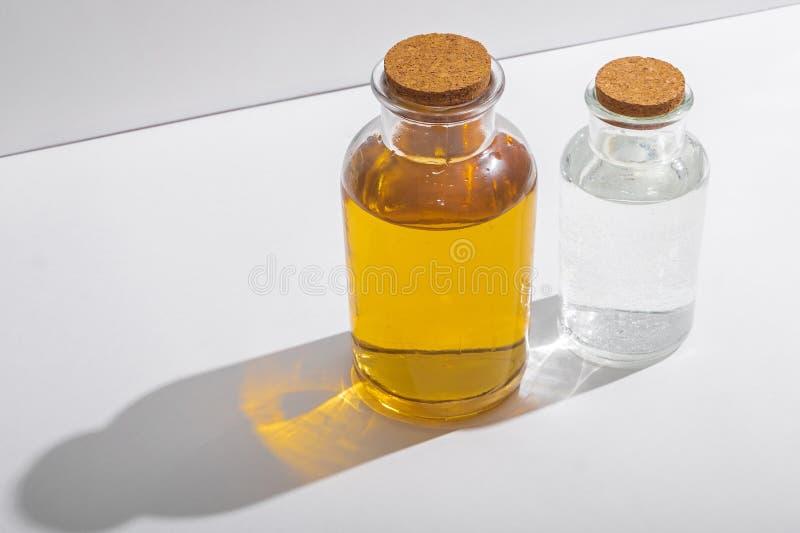 Bottiglie di vetro con i coperchi del sughero su un fondo bianco, vista laterale immagini stock libere da diritti