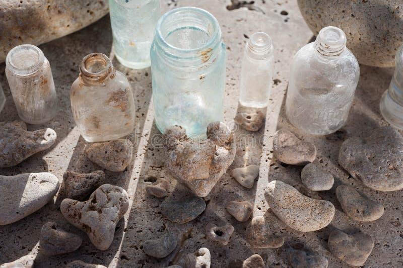 Bottiglie di vetro d'annata e cuori di pietra fotografia stock