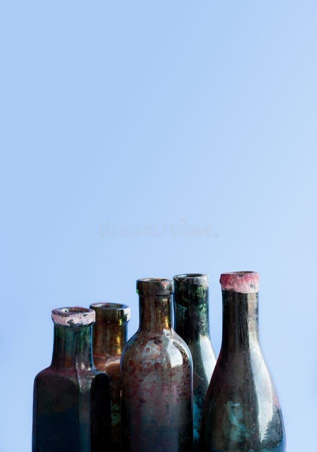 Bottiglie di vetro di progettazione antica su fondo blu Insieme sporco invecchiato variopinto del flacon copi lo spazio, foto ver immagini stock libere da diritti