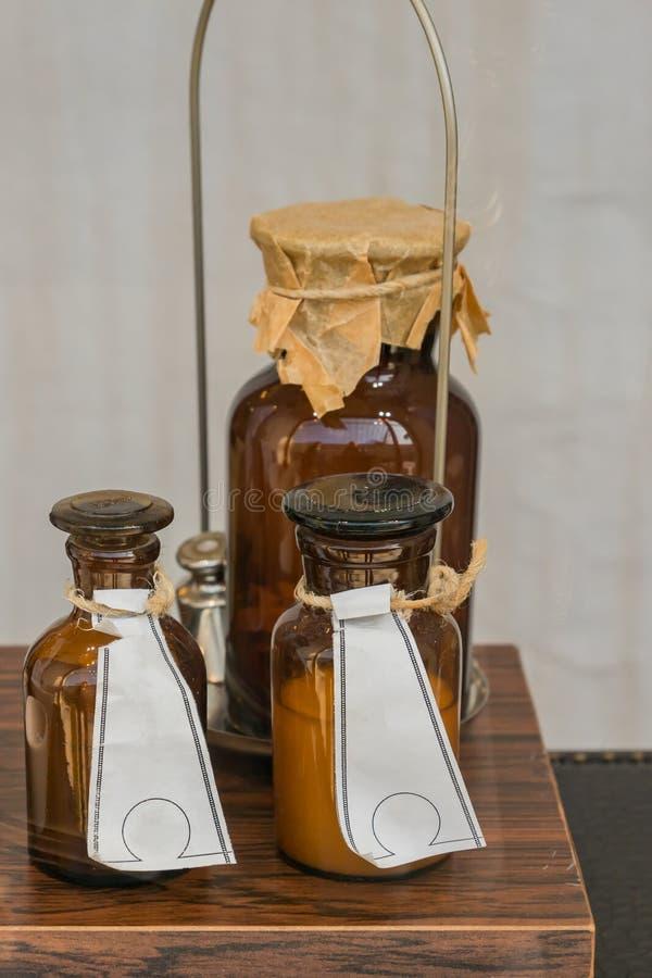 Bottiglie di vetro marroni della medicina d'annata sulla tavola Al negozio della farmacia fotografie stock libere da diritti