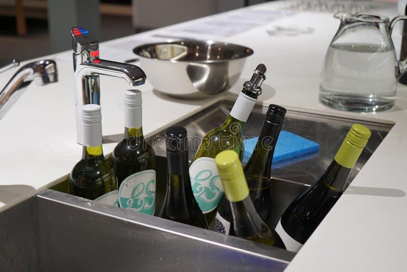 Bottiglie di vino che è raffreddato in un bagno del lavandino in pieno di ghiaccio e di acqua immagini stock