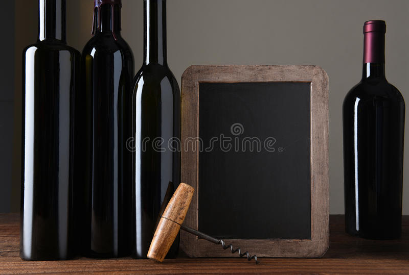 Bottiglie di vino e bordo di gesso immagine stock libera da diritti
