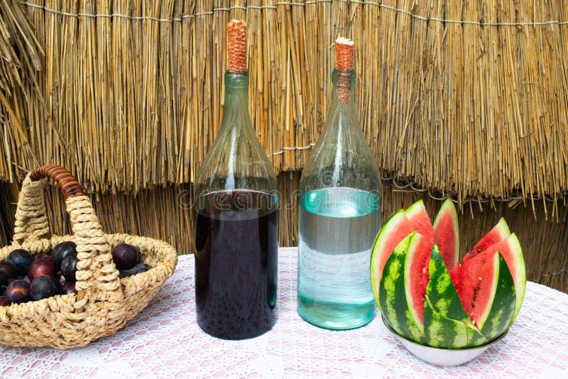 Bottiglie di vino e del chiaro di luna sulla tavola immagini stock