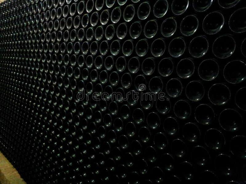 Bottiglie di vino impilate nel magazzino della cantina immagini stock libere da diritti