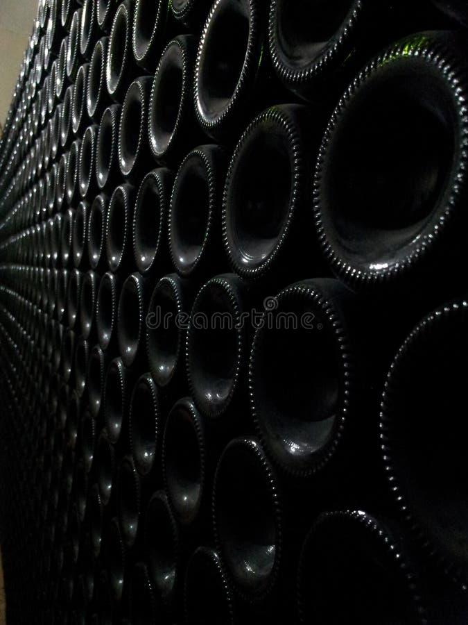 Bottiglie di vino impilate nel magazzino della cantina fotografia stock