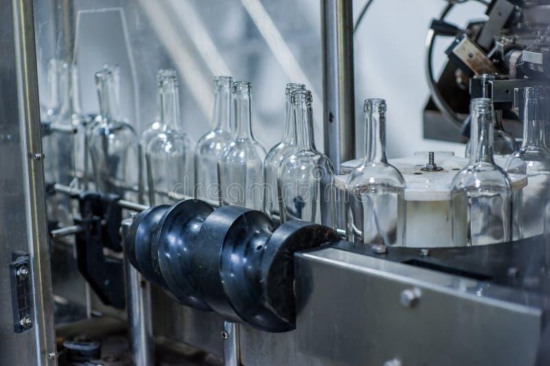 Bottiglie di vino sulla macchina nella fabbrica di produzione fotografia stock
