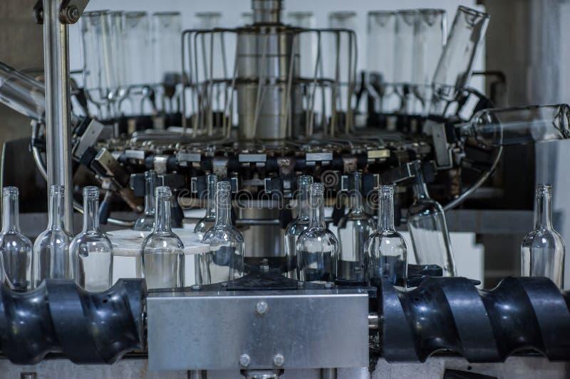 Bottiglie di vino sulla macchina nella fabbrica di produzione fotografie stock