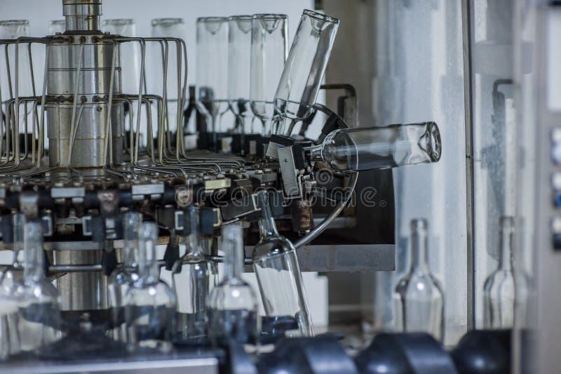 Bottiglie di vino sulla macchina nella fabbrica di produzione fotografie stock libere da diritti