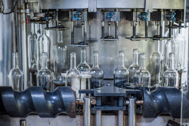 Bottiglie di vino sulla macchina nella fabbrica di produzione immagini stock libere da diritti
