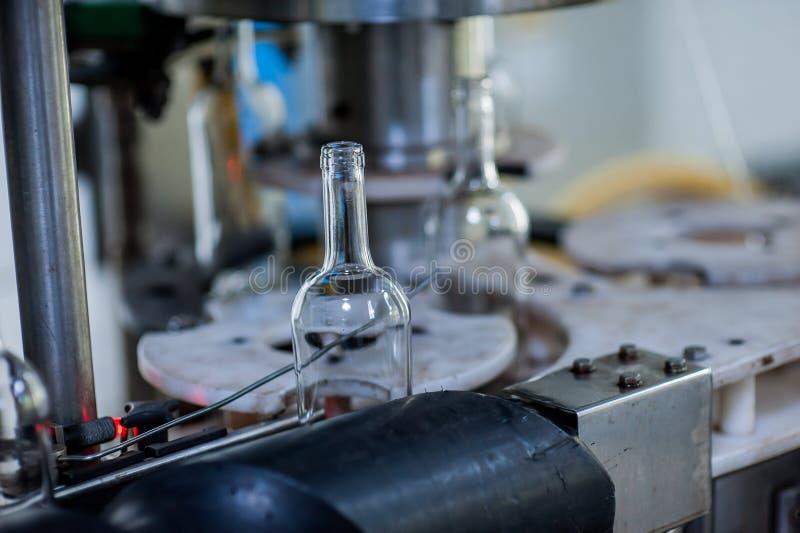 Bottiglie di vino sulla macchina nella fabbrica di produzione immagine stock