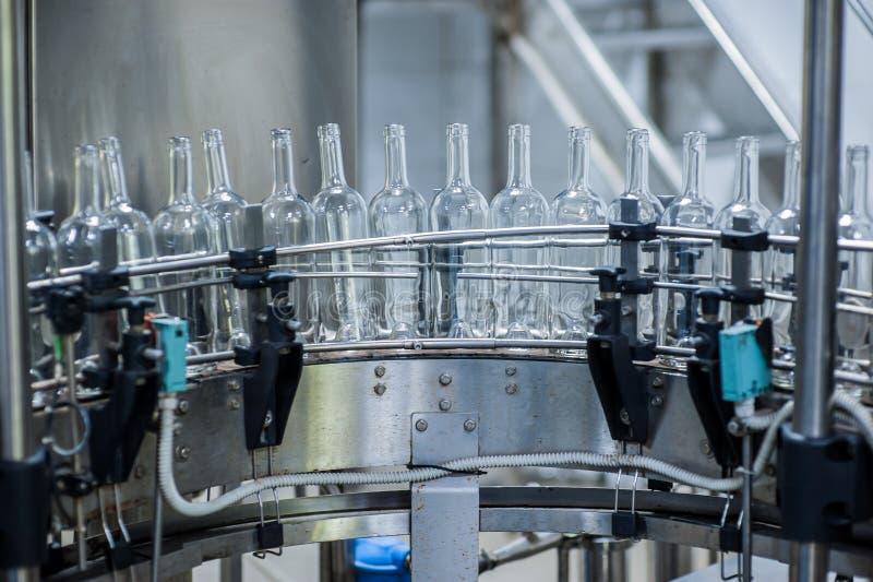 Bottiglie di vino sulla macchina nella produzione fotografia stock