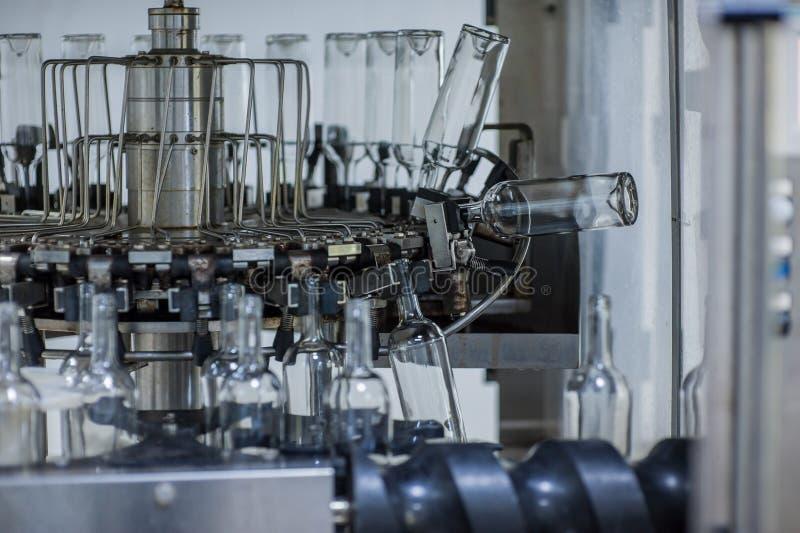 Bottiglie di vino sulla macchina nella produzione immagini stock