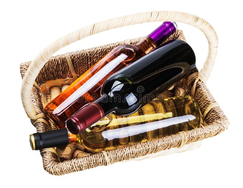 Bottiglie di vino in un canestro isolato su un bianco fotografia stock