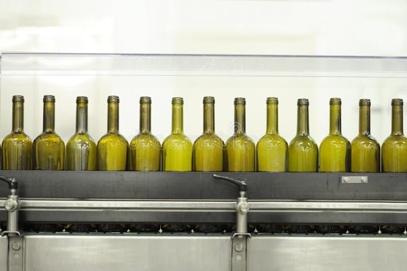 Bottiglie di vino vuote su una riga di riempimento fotografia stock libera da diritti