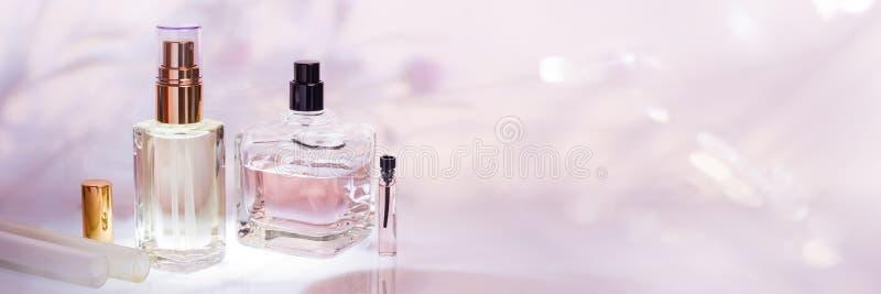 Bottiglie e campionatore di profumo differenti su un fondo floreale rosa Raccolta della profumeria, insegna dei cosmetici fotografia stock