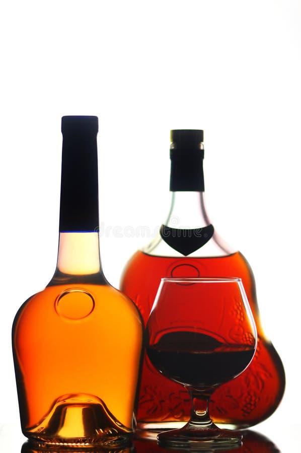 Bottiglie e vetro del cognac fotografia stock