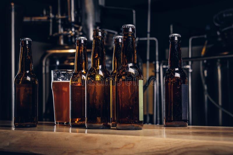 Bottiglie e vetro della birra del mestiere sul contatore di legno della barra alla fabbrica di birra indipendente fotografie stock libere da diritti