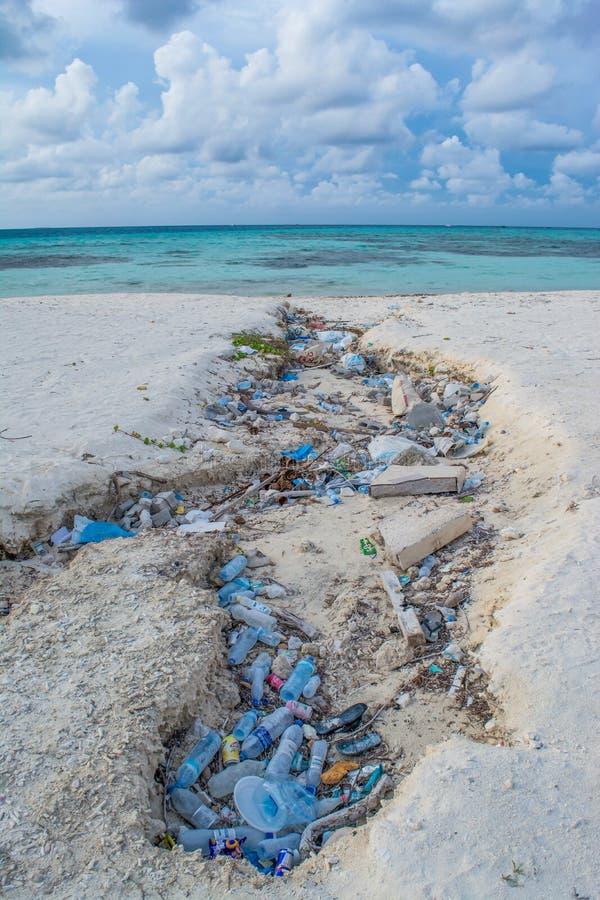 Bottiglie ed immondizia di plastica alla spiaggia tropicale fotografia stock libera da diritti