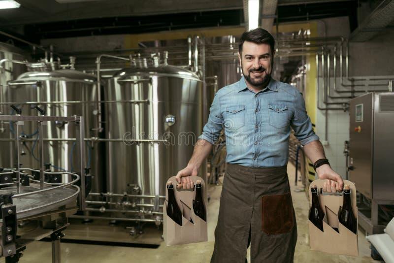 Bottiglie felici della tenuta dell'uomo di alcool in fabbrica di birra fotografie stock