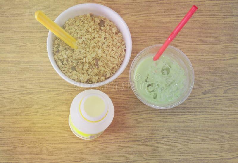 Bottiglie per il latte, tè verde fresco, cucchiaiata gialla delle ciotole di cereale sui pavimenti di legno, luce solare di matti fotografia stock