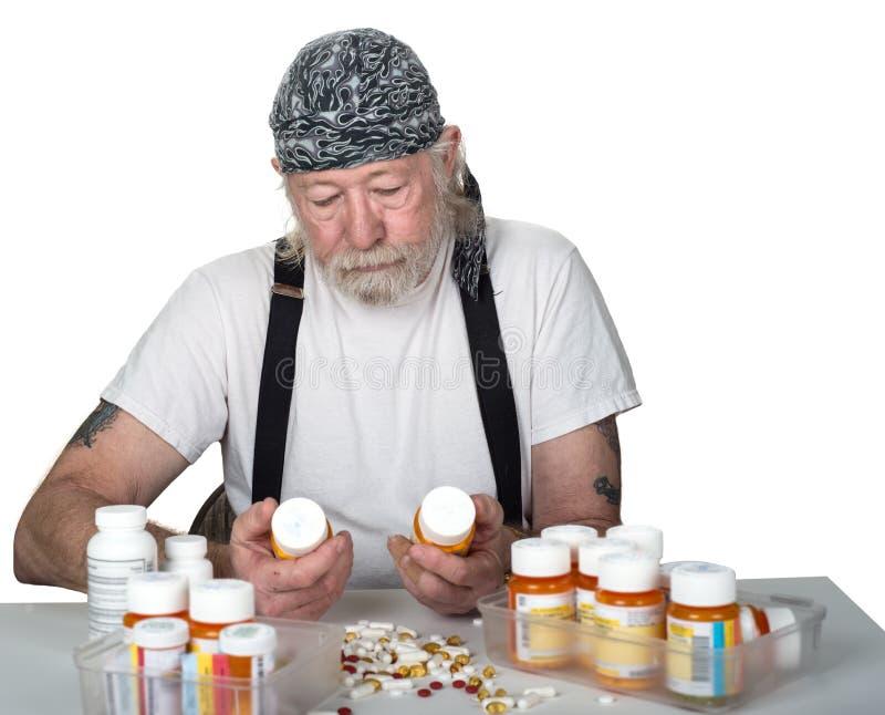 Bottiglie senior di prescrizione della tenuta con le pillole sulla tavola immagini stock libere da diritti