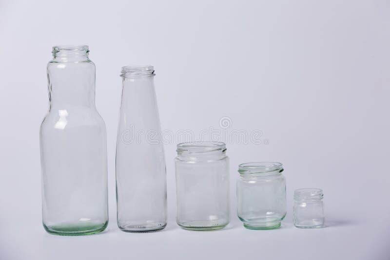 Bottiglie trasparenti di vetro Bottiglie trasparenti di vetro delle dimensioni diverse da grande a piccolo su un fondo bianco fotografia stock