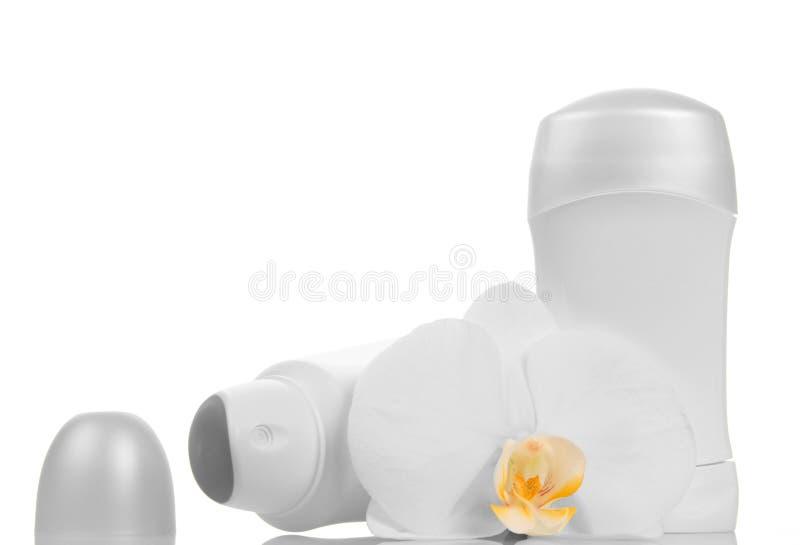 Bottiglie vuote dei deodoranti e del fiore dell'orchidea isolato su bianco fotografia stock