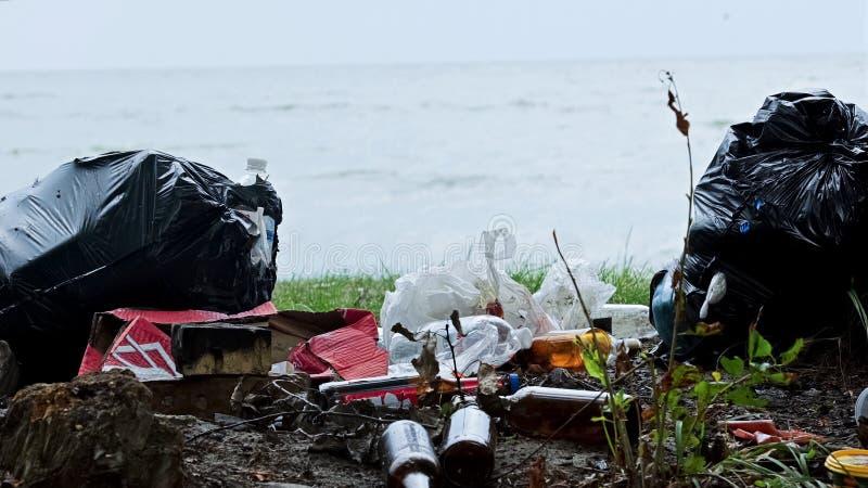 Bottiglie vuote e contenitori che inquinano spiaggia, tonnellate di natura offensiva dell'immondizia fotografie stock