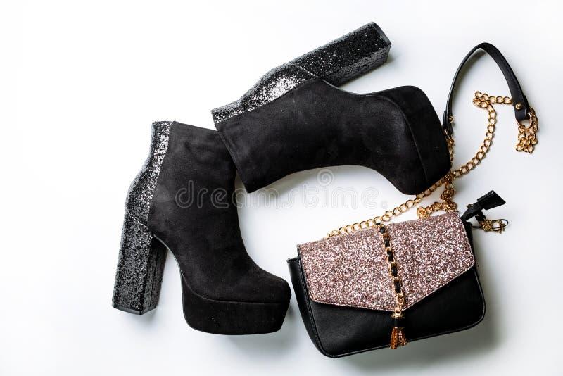 Bottines noires de suède sur une plate-forme et des talons épais avec des étincelles et un sac noir avec des étincelles sur l'ail photo stock