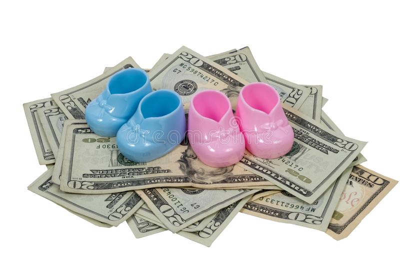 Bottini blu e rosa del bambino su un mucchio di una Bi di venti e dieci dollari fotografia stock