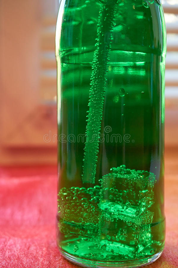 Bottle of aerated water with straw. Closeup of bottle of aerated green water with drinking straw with air bubbles and ice cubes stock photos